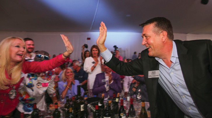 Andy Anderson, right, is congratulated after securing a winning bid at the 2020 Naples Winter Wine Festival auction at The Ritz-Carlton Golf Resort, Naples. ERIC STRACHAN / FLORIDA WEEKLY