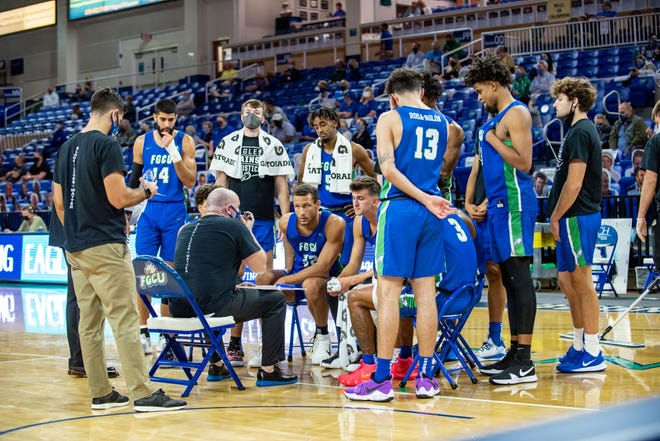 FGCU head coach Michael Fly, seated in black, talks to his team during a timeout in the Eagles' 69-60 victory over North Alabama on Saturday, Feb. 6, 2021 at Alico Arena.