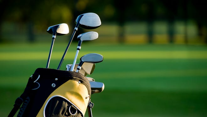 A line of golf clubs on a golf course.